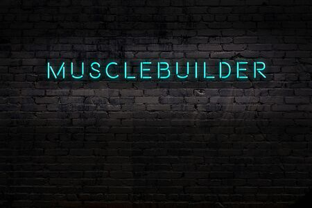 Neon sign with inscription musclebuilder against brick wall. Night view
