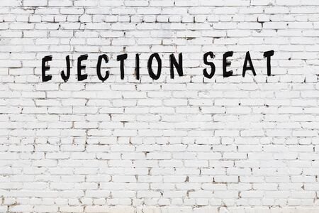 Word ejection seat written with black paint on white brick wall.