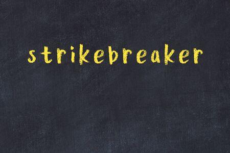 Chalk handwritten inscription strikebreaker on black desk