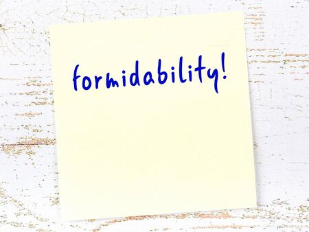 Yellow sticky note on wooden wall with handwritten inscription formidability