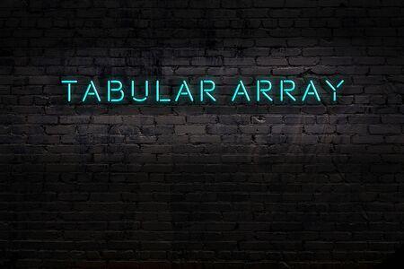 Neon sign on brick wall at night. Inscription tabular array