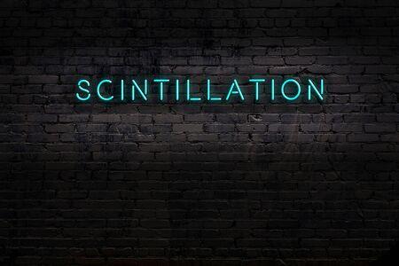 Neon sign on brick wall at night. Inscription scintillation Imagens