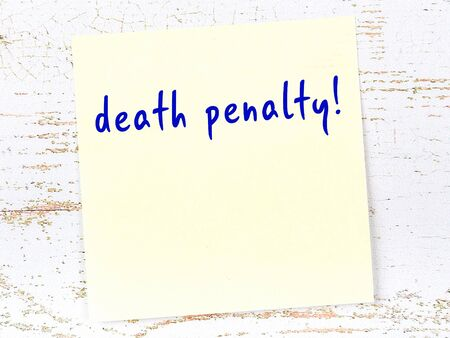 Yellow sticky note on wooden wall with handwritten inscription death penalty