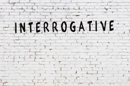 Word interrogative written with black paint on white brick wall.