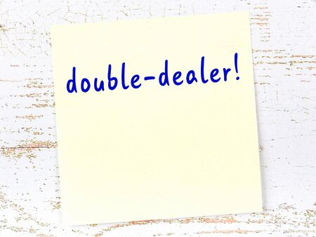 Yellow sticky note on wooden wall with handwritten inscription double-dealer Stock Photo