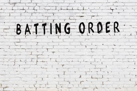 Word batting order written with black paint on white brick wall.