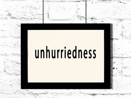 Black wooden frame with inscription unhurriedness hanging on white brick wall 스톡 콘텐츠