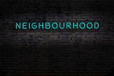 Neon sign with inscription neighbourhood against brick wall. Night view