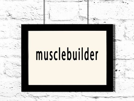 Black wooden frame with inscription musclebuilder hanging on white brick wall Standard-Bild