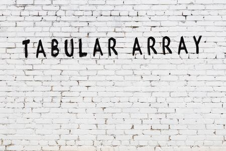 Word tabular array written with black paint on white brick wall.