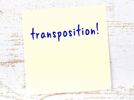 Concept of reminder about transposition. Yellow sticky sheet of paper on wooden wall with inscription
