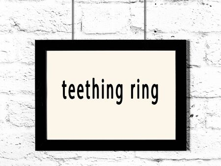 Black wooden frame with inscription teething ring hanging on white brick wall Stock Photo
