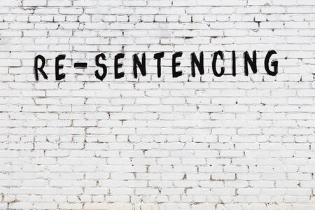 White brick wall with inscription re-sentencing handwritten with black paint