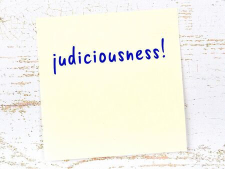 Concept of reminder about judiciousness. Yellow sticky sheet of paper on wooden wall with inscription