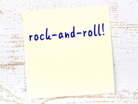 Concept of reminder about rock-and-roll. Yellow sticky sheet of paper on wooden wall with inscription
