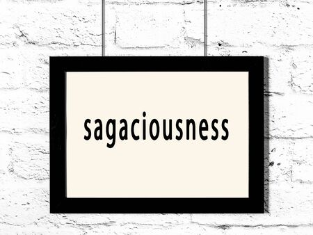 Black wooden frame with inscription sagaciousness hanging on white brick wall Imagens