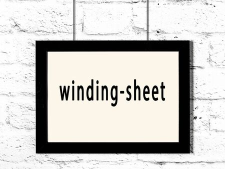 Black wooden frame with inscription winding-sheet hanging on white brick wall