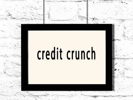 Black wooden frame with inscription credit crunch hanging on white brick wall