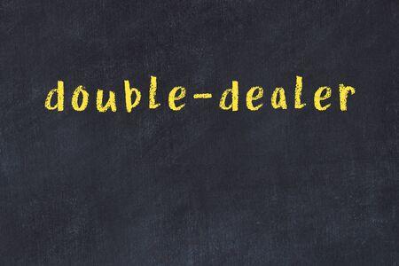 Chalk handwritten inscription double-dealer on black desk