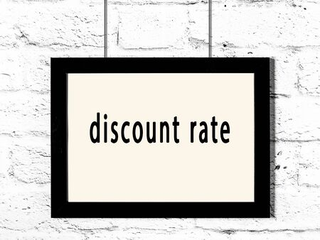 Black wooden frame with inscription discount rate hanging on white brick wall
