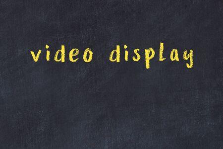 Chalk handwritten inscription video display on black desk Archivio Fotografico