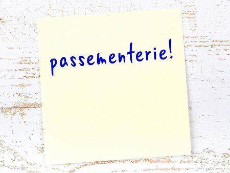 Concept of reminder about passementerie. Yellow sticky sheet of paper on wooden wall with inscription