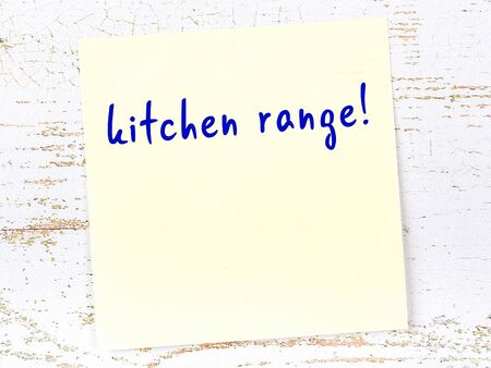 Yellow sticky note on wooden wall with handwritten inscription kitchen range