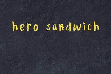 Chalk handwritten inscription hero sandwich on black desk