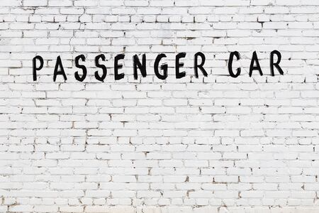 Word passenger car written with black paint on white brick wall.