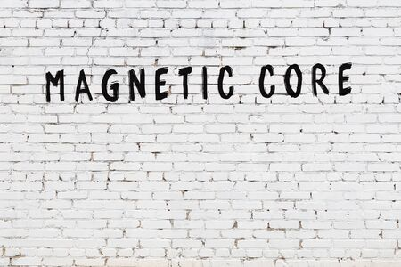 Word magnetic core written with black paint on white brick wall.