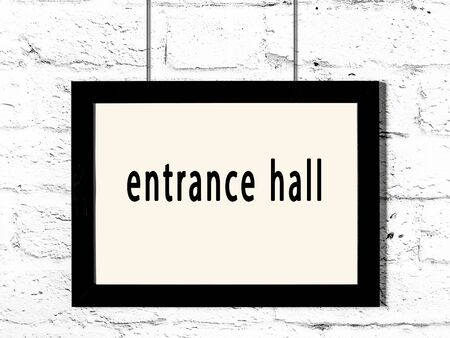 Black wooden frame with inscription entrance hall hanging on white brick wall