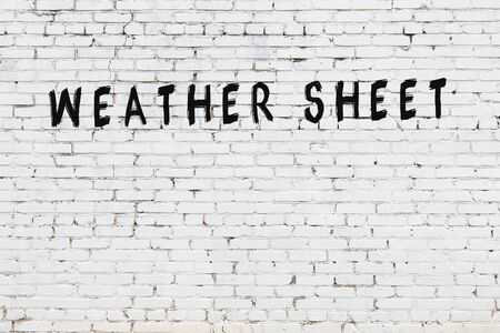 White brick wall with inscription weather sheet handwritten with black paint