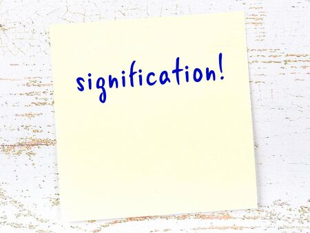 Concept of reminder about signification. Yellow sticky sheet of paper on wooden wall with inscription Archivio Fotografico