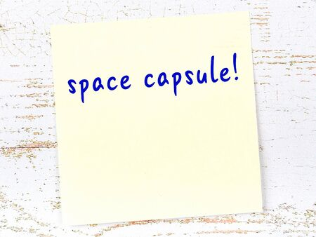 Yellow sticky note on wooden wall with handwritten inscription space capsule Archivio Fotografico