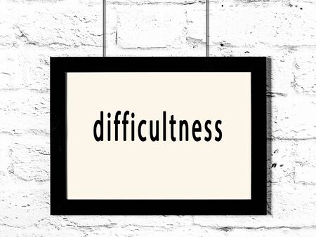 Black wooden frame with inscription difficultness hanging on white brick wall