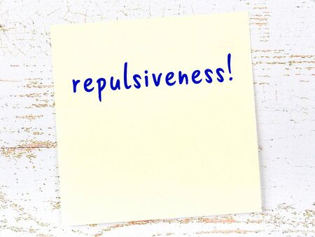 Concept of reminder about repulsiveness. Yellow sticky sheet of paper on wooden wall with inscription
