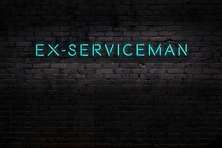 Neon sign with inscription ex-serviceman against brick wall. Night view