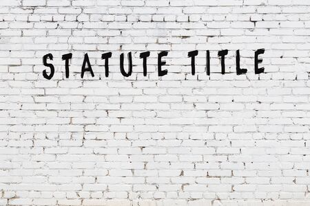 White brick wall with inscription statute title handwritten with black paint