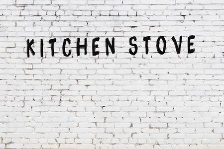 Word kitchen stove written with black paint on white brick wall.