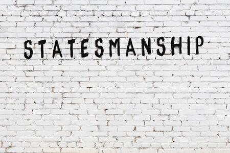 Word statesmanship written with black paint on white brick wall.