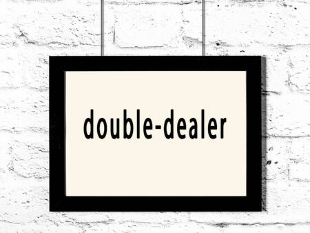 Black wooden frame with inscription double-dealer hanging on white brick wall