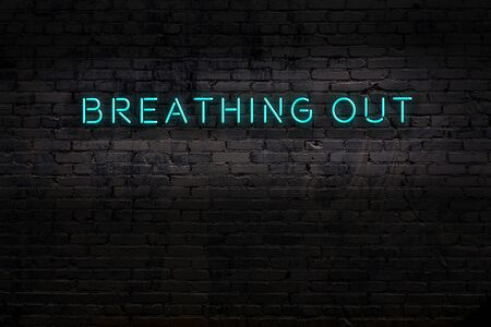 Neon sign on brick wall at night. Inscription breathing out