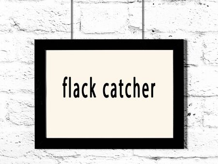 Black wooden frame with inscription flack catcher hanging on white brick wall