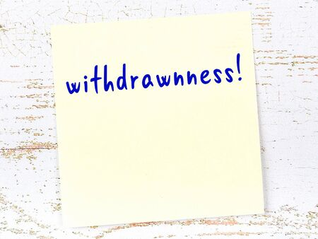 Yellow sticky note on wooden wall with handwritten inscription withdrawnness