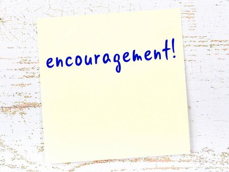 Yellow sticky note on wooden wall with handwritten inscription encouragement