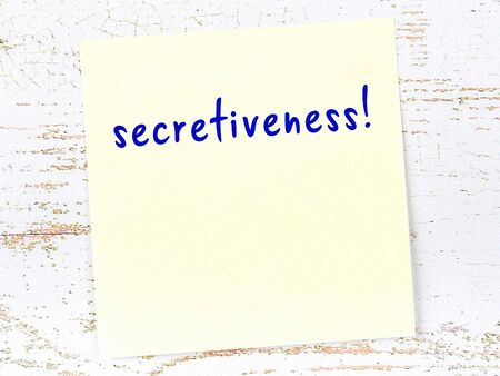 Yellow sticky note on wooden wall with handwritten inscription secretiveness