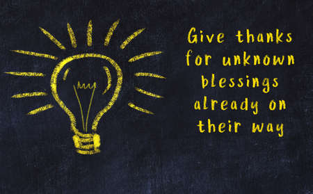 Wise quotation and a chalk drawing of a bulb on black chalkboard Reklamní fotografie