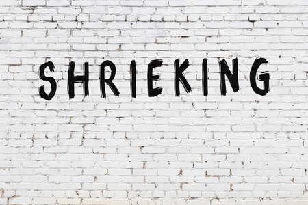 White brick wall with inscription shrieking handwritten with black paint