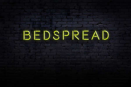 Neon sign with inscription bedspread against brick wall. Night view