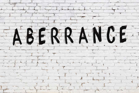 White brick wall with inscription aberrance handwritten with black paint